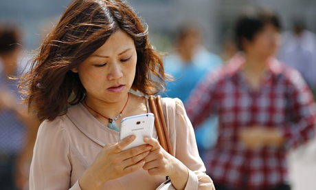 A woman looks at her smartphone in Shanghai